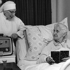 Thumbnail and detail of bedroom in a nursing home, in black and white. An elderly woman in the bed, with a book, smiling. There's a nun in habit at bedside, also smiling, with a radio in front of her.
