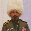 Thumbnail and detail of soldier in tall white fur hat and dressed in old fashioned dark green uniform, standing in front of a house and a yurt.