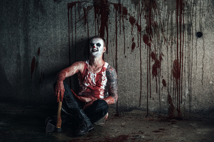 Somewhat gory staged photo of a man with clown makeup, sitting on the ground, holding a hatchet, with blood on his shirt. Illustrates a case study about an order of attachment