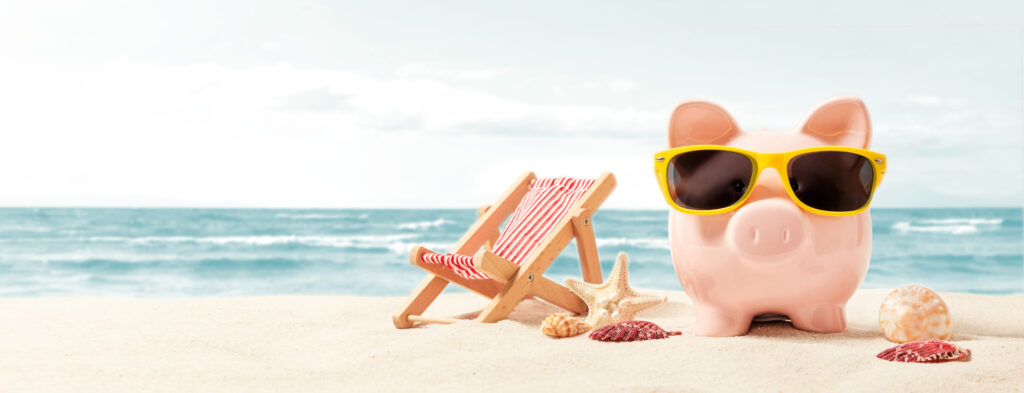 Pink piggy bank wearing yellow sunglasses, setting next to a beach chair and shells on a white sand beach.
